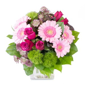 Harmonie, bouquet rond avec des roses fushias, des germinis roses, des œillets et travail de feuillage