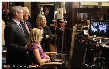 (clockwise) Rachel Harper (sitting), Prime Minister Stephen Harper, Phil Lind (Vice Chairman, Rogers Communications Inc.), and Christina Jennings (Chairman & CEO, Shaftesbury Films) enjoy a behind-the-scenes look at Shaftesbury Films' international hit series Murdoch Mysteries airing on Citytv in Canada. (CNW Group/Shaftesbury Films Inc.)