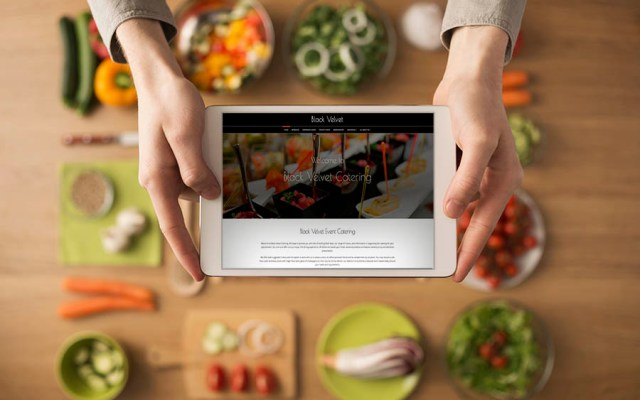 Hands holding a digital touch screen tablet with fresh vegetables and kitchen utensils on background, top view