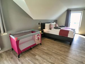 large bedroom with baby bed and ensuite