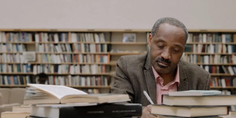man in gray suit jacket sitting beside books