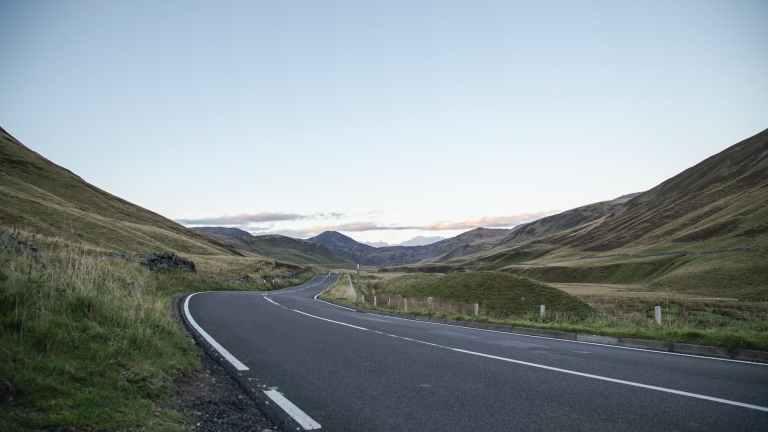 asphalt road through hilly terrain to mountain