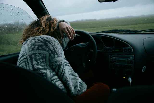 unrecognizable woman sitting in car