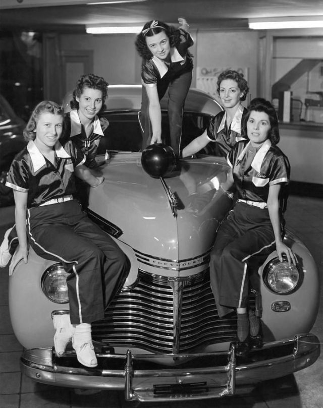 A women's bowling team poses on the front of Chevrolet in a showroom. San Francisco, California 1945