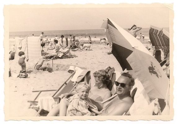 1950s vintage image of family on the beach black and white photo
