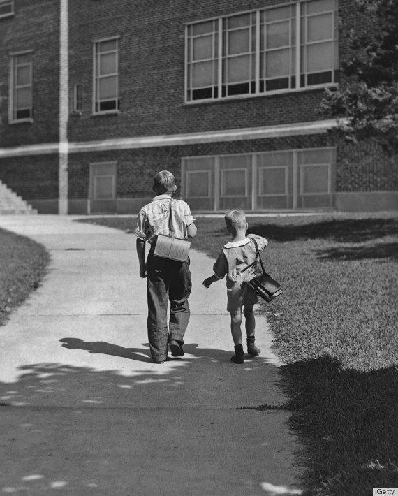 Two small boys, carrying a satchels, walks to school circa 1930's.
