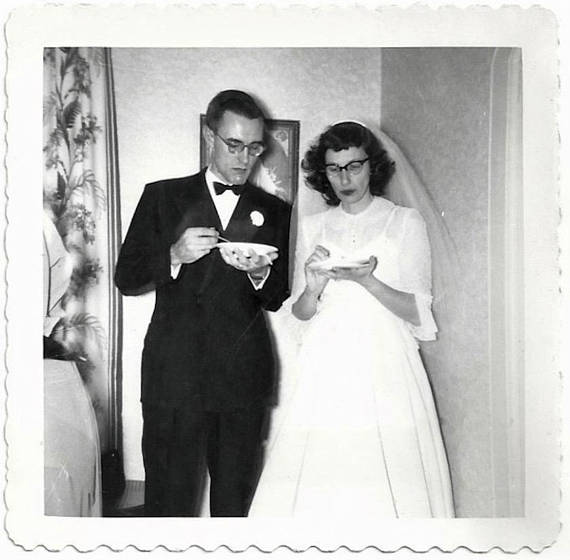 1950s vintage photo of a bride and groom wearing glasses and eating wedding cake