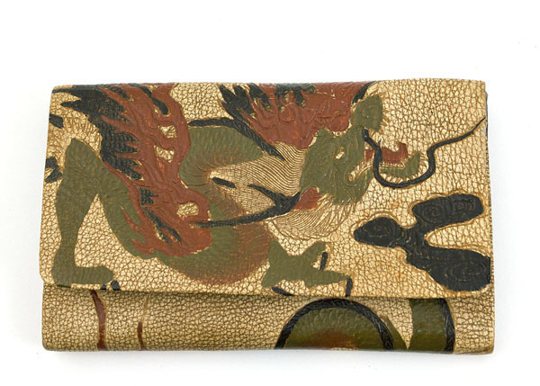 Japanese painted leather wallet, 1920s The wallet came from a New England estate along with several very high end dresses from the same period. Our captivating wallet personifies the style of its owner: individual, brilliant, and impulsive. The leather wallet is embossed and painted with a fiery dragon. It is lined with printed navy/white cotton. The interior has two compartments, one with a fold over flap.