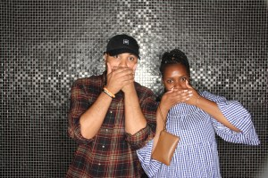 Couple cover their mouths at the Party Photo Booth