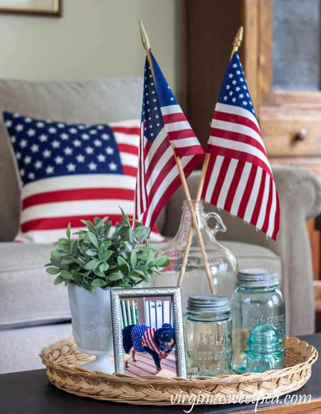 Patriotic Vignete with vintage Mason jars, vintage clear glass jug holding flags, and white milk glass compote with a faux plant and an American flag pillow in the background
