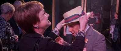 A woman touches the hat of an actor