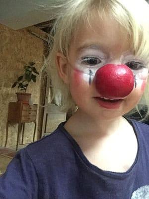 Photo d'une petite fille avec un nez de clown