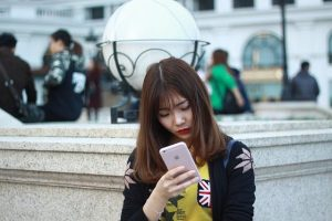A woman watches video content on her mobile device.