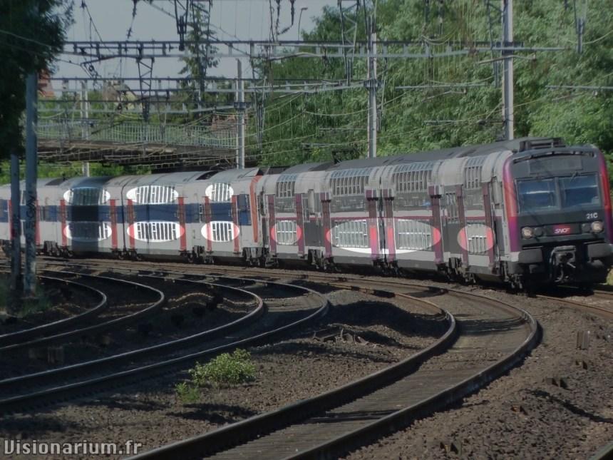 Devant : vieux train avec barres à toutes les fenêtres. Derrière : Z20900 panoramique.