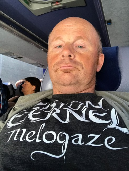 "Christophe Szpajdel wearing his Vision Éternel t-shirt on the plane on his way to the ""A Journey Into The Lost Homelands"" exhibition."