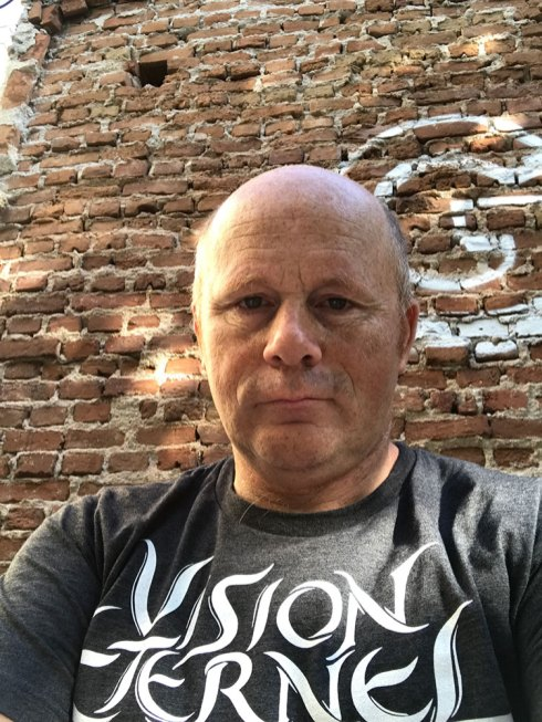 "Christophe Szpajdel wearing his Vision Éternel t-shirt outside the Young Freedom Cafe in Drama, Greece for the ""A Journey Into The Lost Homelands"" exhibition."