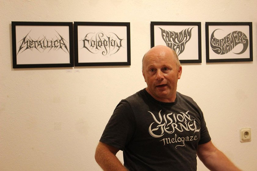"""Christophe Szpajdel wearing his Vision Éternel t-shirt at the """"A Journey Into The Lost Homelands"""" exhibition."""