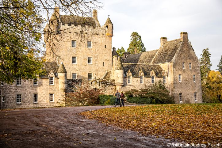Cawdor Caste, a 15th century private fortress, built by the Thanes of Cawdor around a medieval tower house. Couple walking in the grounds. Cawdor Castle is open for private tours by appointment only October to May.