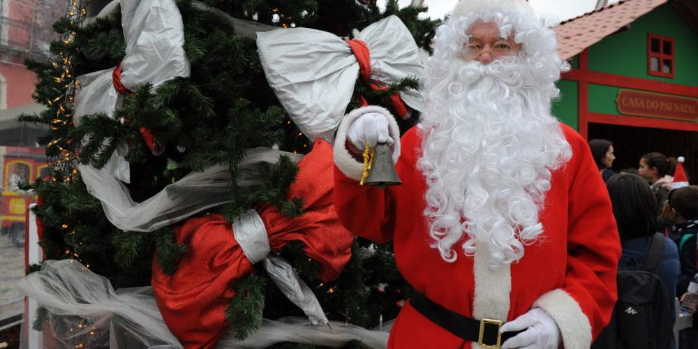 Papai Noel segurando um sino, em frente à uma árvore de natal