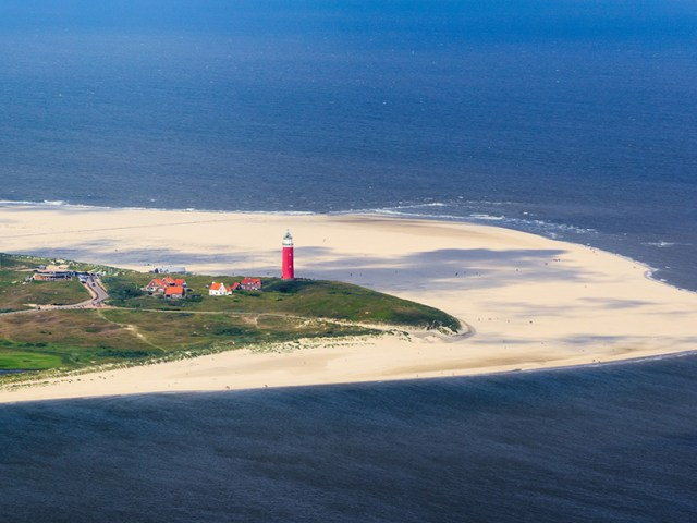 One of the Dutch wadden islands called texel from a bird view. You see the red lighthouse and a sandbank and beach that surrounds the islands with vegetation in the middle.