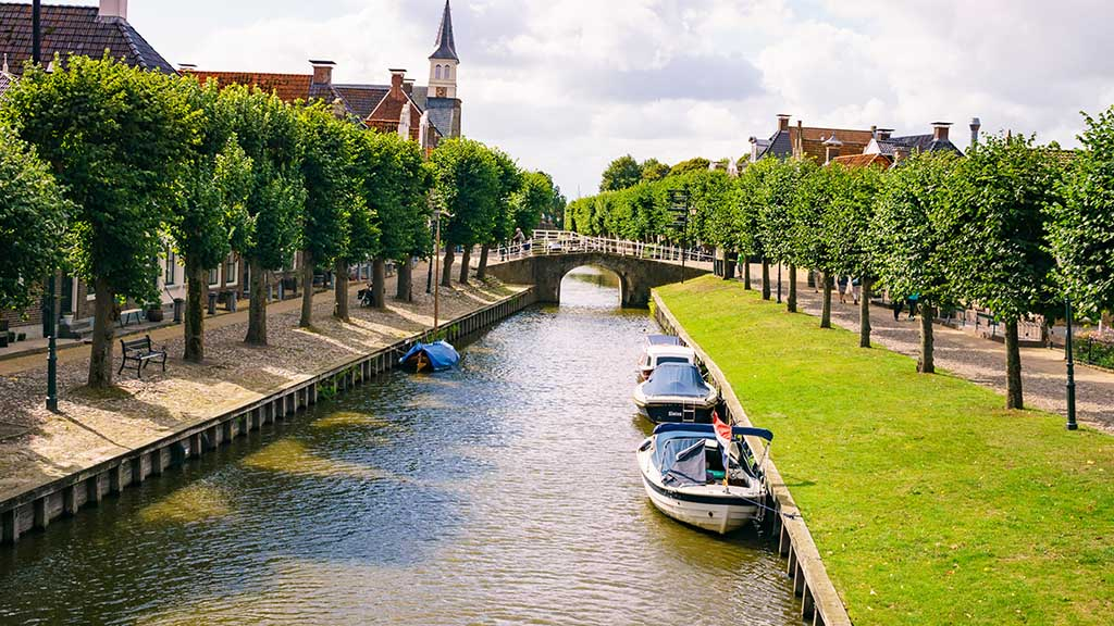 View on a canal surrounded by trees in the town of Sloten, The Netherlands