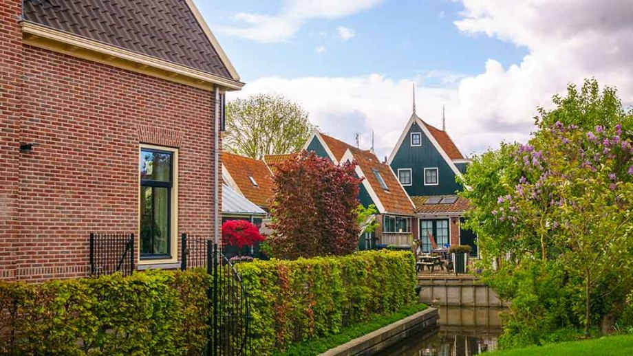 One of the most beautiful small towns of The Netherlands: De Rijp. Here you can see one of the canals and most beautiful streets of De Rijp and its traditional fishing houses. You see a small the back of some canal houses that are painted green blueish and a small part of the canals.