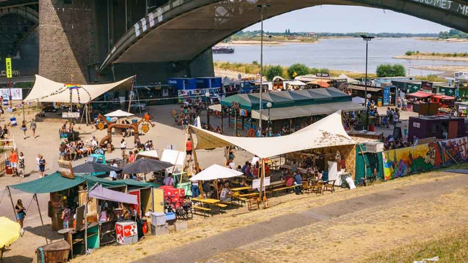 Little street food places and bars under a bridge in the city of Nijmegen during the four days marches in The Netherlands. With a view of the Waal river in the back.