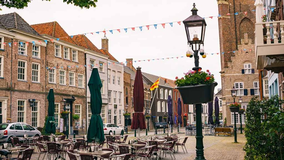 The main square of Grave with tables and historic canal houses in The Netherlands