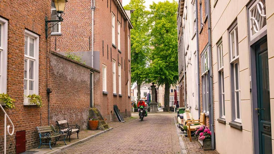 A cyclist drives through a medieval street in the town of Grave, The Netherlands