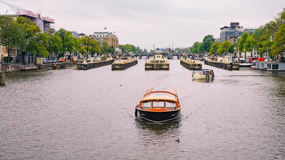 One of the many canal cruise tours, sailing through the canals of Amsterdam, with the city in the background