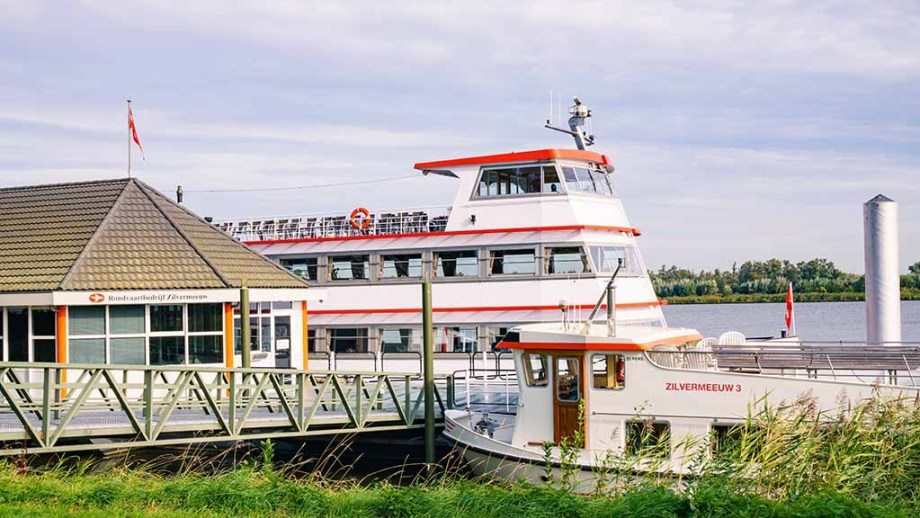 A white and red small cruise boat in the Dutch village of Drimmelen, which gives tours in the Biesbosch freshwater tidal system