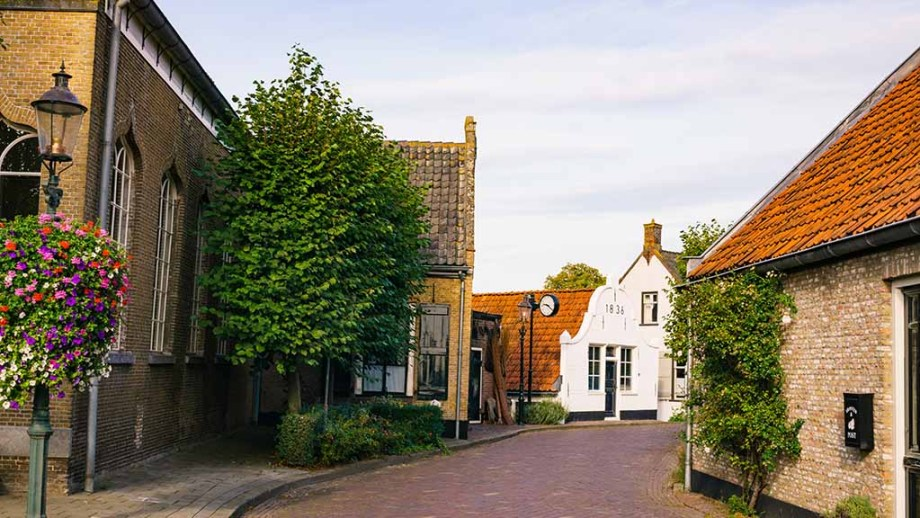 The main street in the village of Drimmelen with historic Dutch buildings and a church on both sides