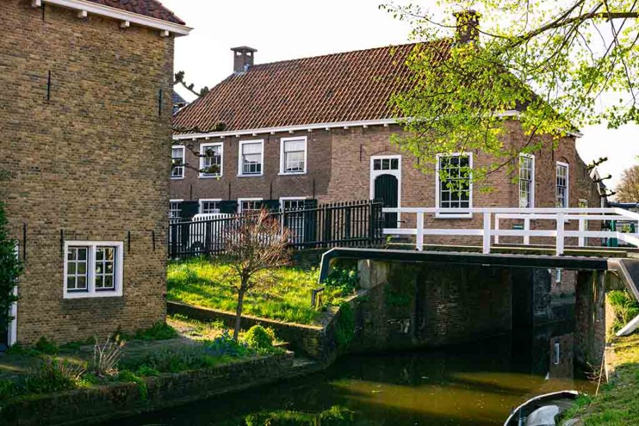 A photo of a bridge and a river surrounded by old brick houses in The Netherlands