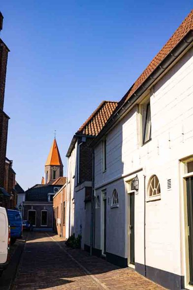 A photo of a cobblestoned street in Montfoort with Dutch white & brown brick houses and a view on an orange church tower