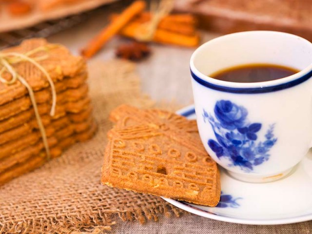 A cup of coffee with traditional Dutch 'speculaas' (spiced shortcrust cookies). Authentic wooden cookie cutters especially made for these cookies can be seen in the background.