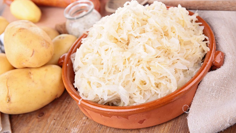 Sauerkraut in a bowl and potatoes, salt and a towel on a wooden table
