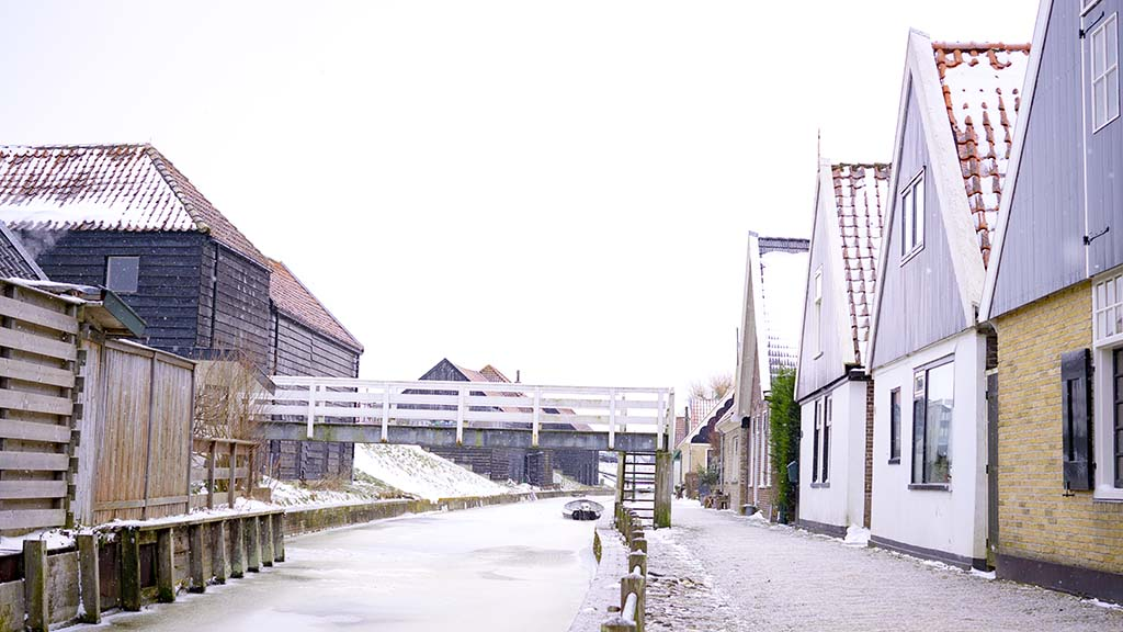 View on a frozen river and snowy cobblestoned street and old Dutch houses in the village of Kolhorn, The Netherlands