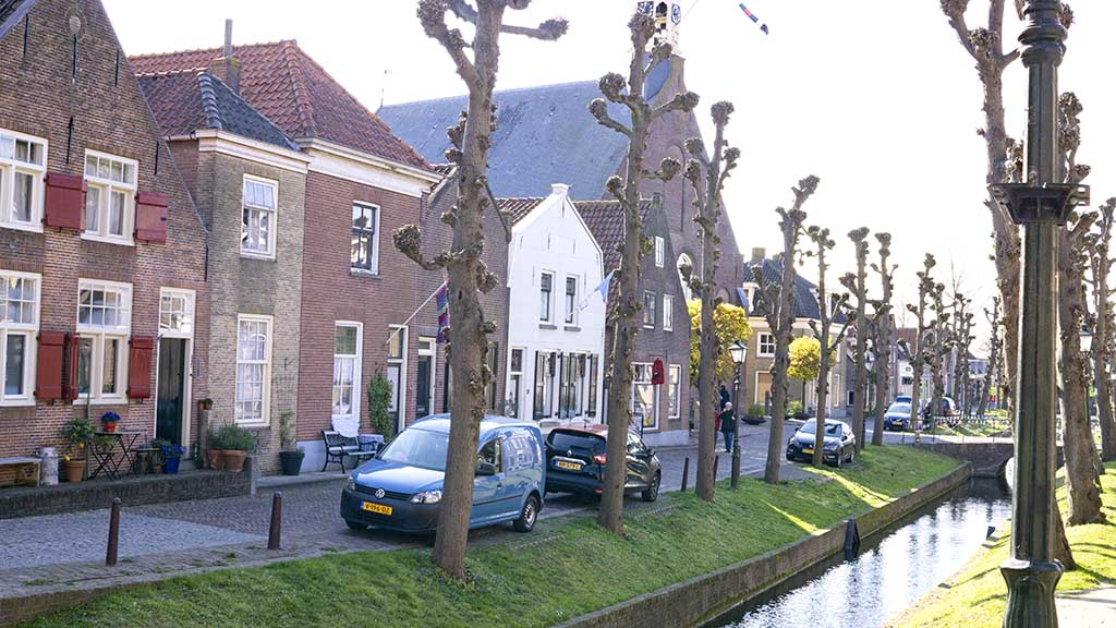 A view on old Dutch brick canal houses behind a canal and trees in the town of Nieuwpoort, The Netherlands