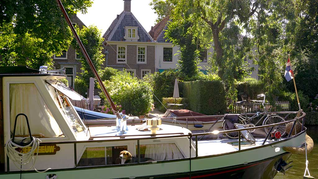 A view of a boat on a river in front of Dutch canal houses in the village of Vreeland, Utrecht, The Netherlands