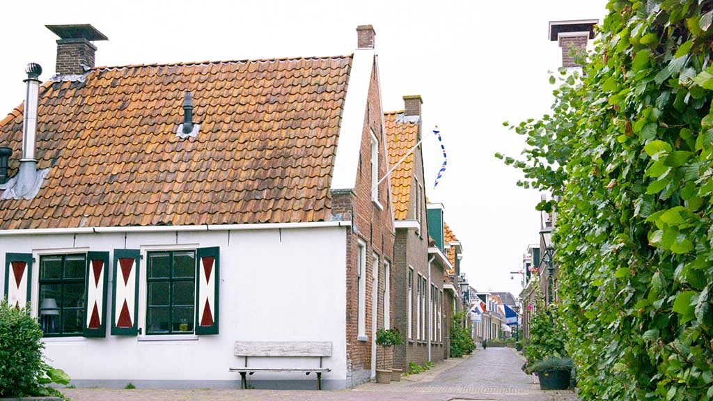 View on an idyllic cobblestoned street with old brick buildings in Woudsend, The Netherlands