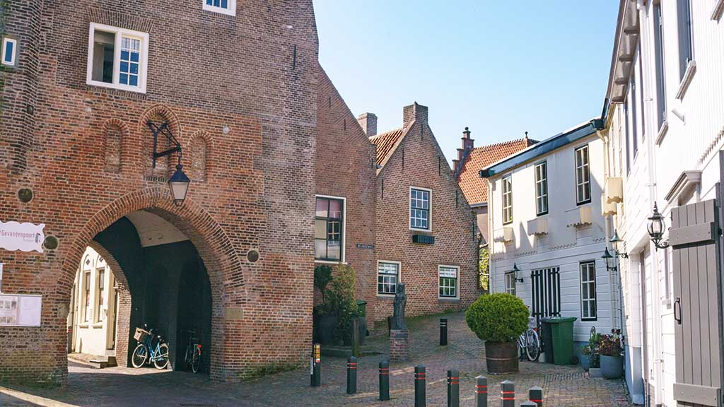 View on a cobblestoned street and brick city gate in the village of Woudrichem