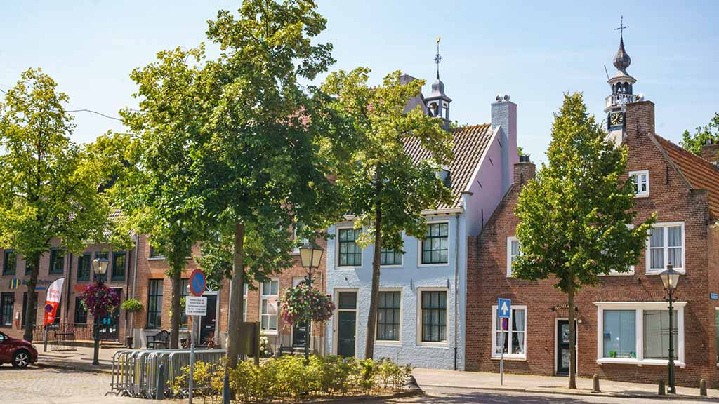 view on beautiful Dutch historic buildings on a square in IJzendijke, Zeeland, The Netherlands