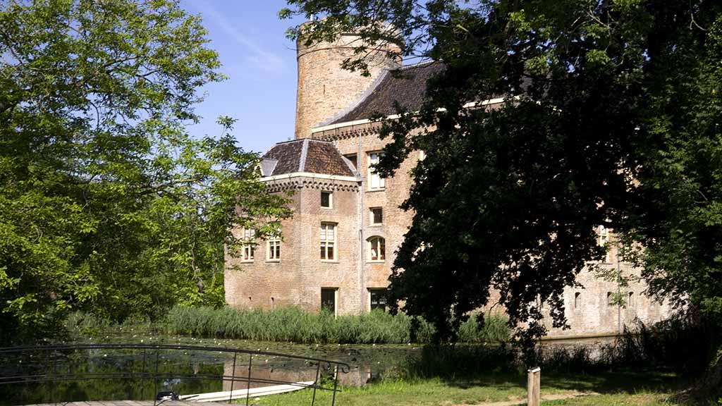 View on the castle of Loenersloot hidden between trees in The Netherlands