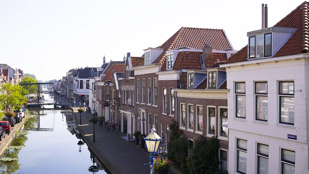 view on a canal that runs through the town of Maassluis and historic canal houses on the side in The Netherlands