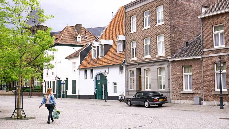 view on woman walking on cobblestoned street with historic buildings in city of Sittard, Limburg, The Netherlands