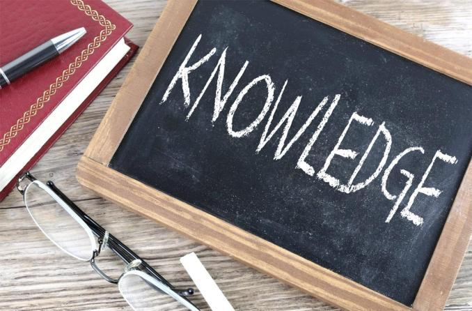The word Knowledge in chalk on a blackboard, a pair of glasses, notebook and pen