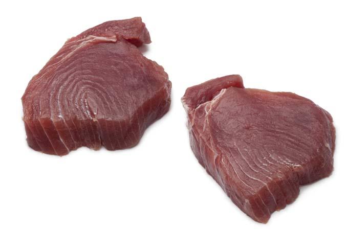 Fresh tuna steaks on white background
