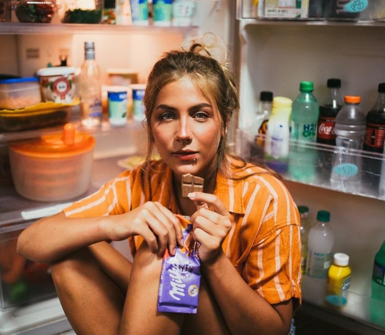 donna mangia cioccolato con il frigo aperto