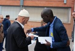 Un voluntari dóna una papereta i explica en què consisteix la votació a un participant // Jose Polo