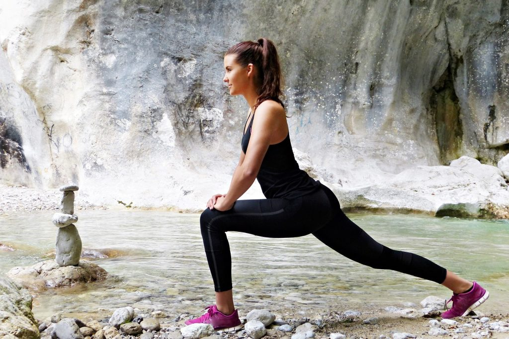 fit young lady wearing black top and thights doing a lunge background stream rock wall, 5-minute workouts, Can Doing 5-Minute Workouts Make You Fit?